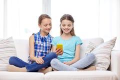 Filles heureuses avec le smartphone se reposant sur le sofa Image stock