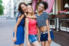 Filles heureuses ayant l'amusement tout en marchant dans la ville Photos stock