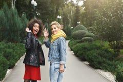 Filles heureuses ayant l'amusement tout en marchant dans le parc Image libre de droits