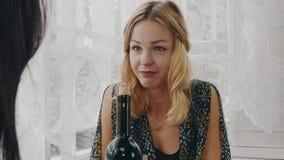 Filles heureuses causant à la table avec la bouteille de vin sur la terrasse de la maison de campagne clips vidéos