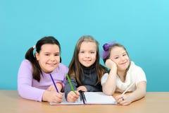 Filles heureuses d'école effectuant leur travail dans la salle de classe Photos libres de droits