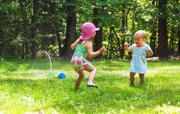 Filles heureuses d'enfant en bas âge jouant dans une arroseuse Photo stock