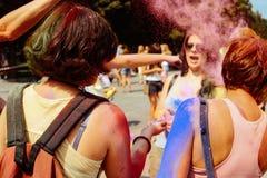 Filles heureuses de hippie ayant l'amusement avec la poudre colorée au fest de holi Photo stock