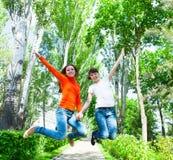 Filles heureuses de jeune adolescent le sautant le parc Images stock