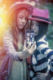 Filles heureuses de l'Asie prenant le selfie au parc Photo libre de droits