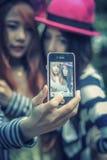 Filles heureuses de l'Asie prenant le selfie au parc Photos stock