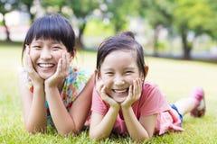 Filles heureuses de plan rapproché petites sur l'herbe Photos libres de droits