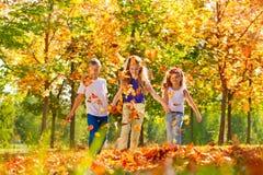 Filles heureuses et garçon jouant dans la forêt ensemble Images libres de droits