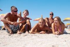 Filles heureuses et types se trouvant sur le sable l'été Photos stock