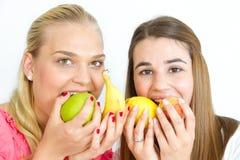 Filles heureuses mangeant des fruits Photos stock