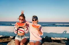 Filles heureuses mangeant la pastèque sur la plage Amitié, happines Photos stock