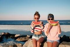 Filles heureuses mangeant la pastèque sur la plage Amitié, happines Images libres de droits