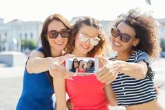 Filles heureuses prenant le selfie dehors dans la ville Images libres de droits