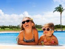 Filles heureuses prenant un bain de soleil dans la piscine extérieure Images libres de droits