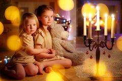 Filles heureuses s'asseyant par une cheminée le réveillon de Noël Images stock