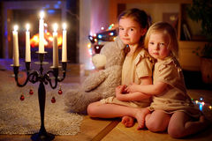 Filles heureuses s'asseyant par une cheminée le réveillon de Noël Images libres de droits