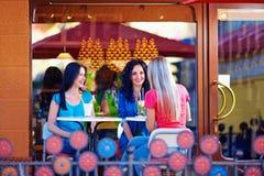 Filles heureuses s'asseyant sur la terrasse de café d'été Image libre de droits