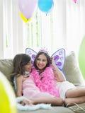 Filles heureuses s'asseyant sur Sofa In Party Costumes Image libre de droits