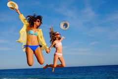 Filles heureuses sautant ensemble sur la plage Images stock