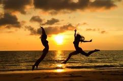 Filles heureuses sautant sur la plage Photo stock
