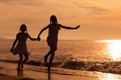 Filles heureuses sautant sur la plage Images libres de droits