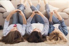 Filles heureuses se trouvant sur le plancher et à l'aide des smartphones Photo stock