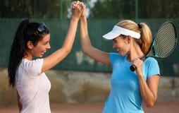 Filles heureuses sur le court de tennis Images stock