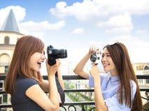 filles heureuses tenant l'appareil-photo et le concept de voyage photo stock