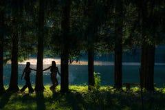 Filles hippies assez libres marchant par les bois Vue de lac - Photos libres de droits