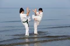 Filles japonaises de karaté s'exerçant à la plage Photos libres de droits