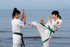Filles japonaises de karaté s'exerçant à la plage Image libre de droits