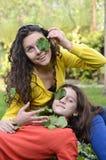 Filles jouant avec des feuilles dans le jardin Image stock