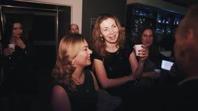 Filles joyeuses ayant des boissons et riant avec l'homme à l'événement de soirée de barre banque de vidéos
