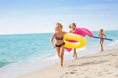 Filles joyeuses dans les vêtements de bain fonctionnant à la plage tropicale Images libres de droits