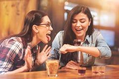 Filles joyeuses faisant des visages tout en appréciant vendredi soir Image libre de droits