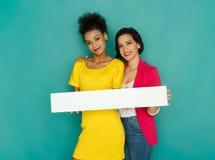 Filles joyeuses tenant le conseil blanc vide au fond de studio d'azur Images libres de droits