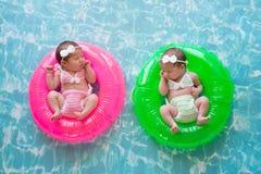 Filles jumelles de bébé flottant sur des anneaux de bain Photographie stock