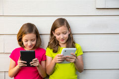 Filles jumelles de soeur jouant avec le PC de comprimé heureux sur le mur blanc Image stock