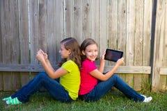 Filles jumelles de soeur jouant le PC de comprimé se reposant sur la pelouse d'arrière-cour Image stock