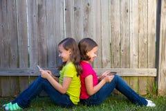 Filles jumelles de soeur jouant le PC de comprimé se reposant sur la pelouse d'arrière-cour Photos stock
