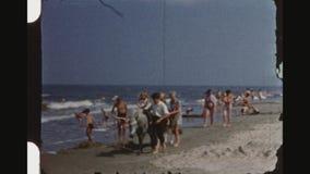 Filles jumelles montant Ponys guidé par deux Young Boys sur la plage banque de vidéos