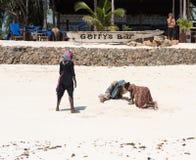 Filles locales cherchant quelque chose sur la plage sablonneuse près de la barre à Zanzibar Image stock