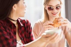 Filles mangeant des croissants et buvant du café au café, pause-café Image stock