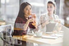 Filles mangeant des croissants et buvant du café au café, pause-café Photos libres de droits