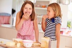 Filles mangeant des ingrédients tout en faisant le fromage sur le pain grillé Photos libres de droits