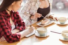 Filles mangeant le gâteau et buvant du café au café, pause-café Image libre de droits