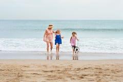 2 filles marchant sur la plage avec la maman et le chien Marche heureuse de famille Photographie stock
