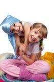Filles mignonnes dans des pyjamas d'isolement sur le blanc Photo libre de droits