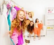 Filles mignonnes heureuses dans la boutique choisissant des vêtements Images stock