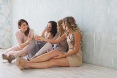 Filles mignonnes, meilleurs amis gais, appréciant la partie, ayant l'amusement, étreignant avec des verres de champagne Robes lum Photo stock
